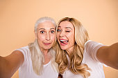 Close up photo of cute lovely childish feel satisfied adults bloggers blogging fool have free time hug embrace leisure wavy grey haircut tongue out isolated wear stylish clothes on beige background