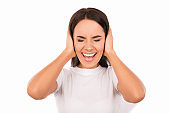 Close up photo of annoyed young woman plugging ears with hands