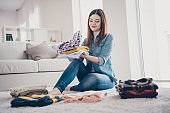 Full length photo of charming dreamy red hair girl hold pile stack of checkered clothes look appreciate new laundry effect chose perfect shirt for husband sit comfort floor carpet outfit indoor