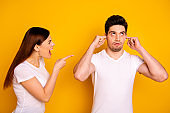 Close up side profile photo two beautiful people she her he him his blaming yell fault aggression awful roll eyes up hide ears fingers ignore wear casual white t-shirts isolated yellow background