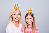 Close up photo cheer two people blond haired she her granny little daughter weekend activities crowns on head stars wear pink plaid checkered shirt sweater pullover isolated light grey background
