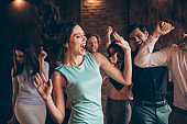 Close up photo classy gathering hang out dancing singing yell scream shout she her ladies hair volume flight blow air wind he him his guys wear dress shirts formal wear sit sofa loft room indoors