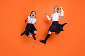 Full length body size view of two person nice attractive charming cheerful cheery pre-teen girls having fun new academic year September a-mark isolated on bright vivid shine orange background