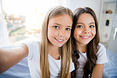 Close up photo of cheerful content children feel satisfied sit bed room indoors