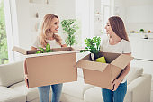 Close up photo two people mum and teen daughter with paper big boxes in arms ready to change decor do repair wear white t-shirts jeans in bright flat stand in front of comfortable sofa