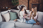 Portrait of two nice lovely adorable attractive charming friendly cheerful girls sharing discussing dream news information memories sitting on divan in house loft industrial interior style