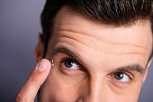 Close up cropped view photo of concentrated lovely pretty handsome millennial use have doctors office service want good eye vision hold hand finger look isolated grey background