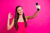 Portrait of her she nice-looking attractive lovable winsome gorgeous cheerful cheery long-haired girl making selfie showing ok-sign isolated over bright vivid shine vibrant pink fuchsia color background