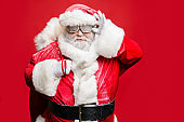 Portrait of smart confident elderly strict santa claus fix his goggles ready to carry his big sack bag with present gifts wear white gloves costume belt cap isolated over red color background