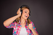 Pretty excited girl in headphones listening music and singing
