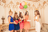 Cute girls give presents with balloons and birthday cake to their friends