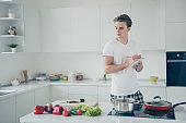 Portrait of his he nice attractive serious focused guy learning making lunch writing notes plan buyings at light white modern style interior house indoors