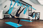Yoga in a white room. Girls performs physical exercises fly-yoga, pilates on a special equipment