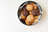 Homemade cookies in round tin box on white background