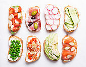 Set of colorful sandwiches prepared with different ingredients such as fish, vegetables and meat. Top view