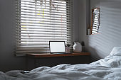 laptop with copy space empty screen and bed with white sheets