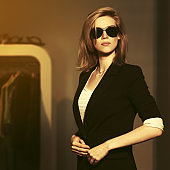 Young fashion blonde woman in sunglasses and black suit jacket