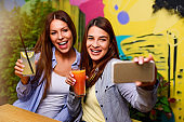 Two Beautiful Young Women Enyoing their time together and making selfies with phone camera