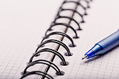 Opened notepad in a cage with an automatic plastic ballpoint pen close-up.