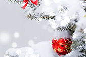 """Christmas tree in snow background. New Year composition with fir tree, balls and lights and bokeh."""" nChristmas and New Year festive background."""