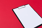 Clipboard with white sheet and pen on a colored background. View from above. space for text