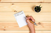 To do list Concept - 2020 number and text on notepad. Woman hand holding blank paper on wooden background.