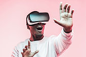 Young african man playing VR video game with virtual reality goggles and mouth wide open, trying to touch something