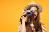 Close-up studio portrait of happy smiling young female tourist holding camera, isolated on yellow background