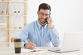 Caucasian male talking on phone and filling papers while working in office