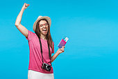 Happy young female expressing joy becaue she finally got tickets and visa for journey, isolated on blue background