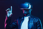 African american man in vr glasses, using virtual reality headset, trying to touch something with finger
