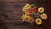 Dry pasta penne, farfalle, tagliatelle with basil and cherry tomatoes on wooden table