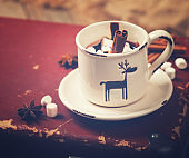 Hot Chocolate with Marshmallow candies. Warming holiday drink with cinnamon sticks . Warm Christmas.Winter Still Life in the Cup.Toned image Vintage style