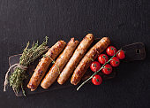 Fried sausages with thyme and tomatoes on a wooden serving Board. Great beer snack on a dark background. Top view with copy space