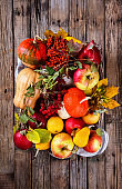 Autumn fruit background. Autumn Thanksgiving seasonal fruit.  Decorative pumpkins,colorful leaves,chestnuts,acorns,Rowan and cranberries .selective focus.