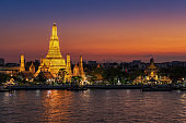 """Wat Arun Temple or """"Temple of Dawn"""" at sunset in Bangkok Thailand and one of Bangkok's most famous landmarks."""
