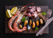 Lots of fresh seafood on a wooden Board. Shrimp, mussels, octopus, greens, lemon, olives. The view from the top.