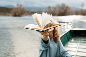 Portrait of young beautiful woman sitting on a boat and reading a book. She is bookworm and she choose between few books. Close up photo, no face shown.