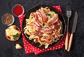 Classic pasta Carbonara, with bacon, egg, Parmesan cheese and Basil on a black slate background. Pieces of Parmesan, Basil, spices, olives and a fork lie near on the table. the view from the top.