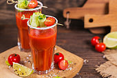 Two glasses of tomato juice decorated with fresh tomatoes, cucumber and leaves on a wooden background