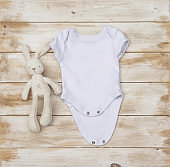 Blank white baby bodysuit/grow with cream rabbit toy on a distressed rustic wooden board mock-up