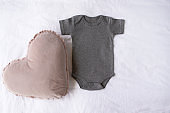 Gray baby onesie bodysuit mock up with a heart cushion prop