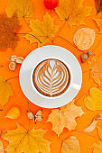 Coffee latte cup in dry autumn leaves wreath frame