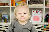 Portrait of sad crying baby girl in the playroom