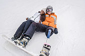 Amputee Snowboarder with African-American woman on the snow