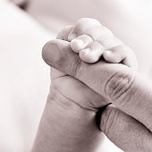 baby gripping the finger of an adult, in black and white