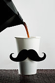 cup with a moustache being filled with coffee