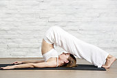 Young woman in the white outfit practicing stretching yoga positions, wellbeing and self care concept