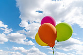 Vibrant colored helium balloons and blue sky