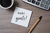 text new goals in a note on a desk